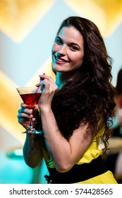 Portrait of beautiful woman having a red martini in bar