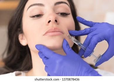 Portrait of beautiful woman having upperlip filler in modern aesthetic clinic