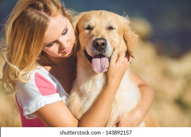 Portrait of beautiful woman with her retreiver dog playing near blue sea
