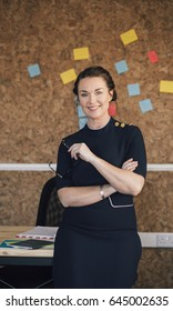 Portrait of a beautiful woman in her workplace. She is standing in front of a corkboard and is smartly dressed, smiling for the camera.