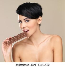 Portrait of beautiful woman, holding chocolate bar