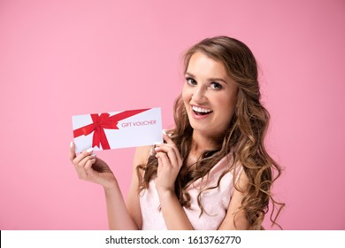 Portrait of beautiful woman holding a gift voucher