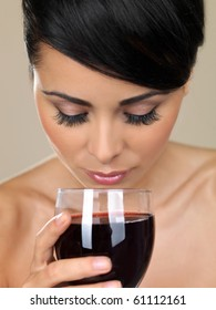 Portrait of beautiful woman, holding glass of red wine