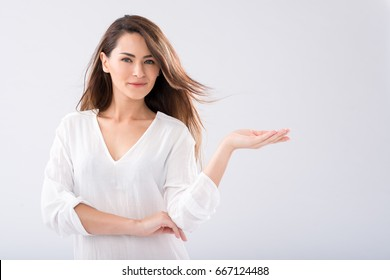 Portrait of beautiful woman holding invisible product in her hand