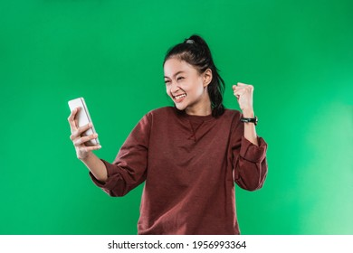 Portrait beautiful woman holding and look handphone with happiness expression while raising one hand and making a fist, isolated on green background