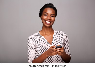 Portrait of beautiful woman holding mobile phone and smiling