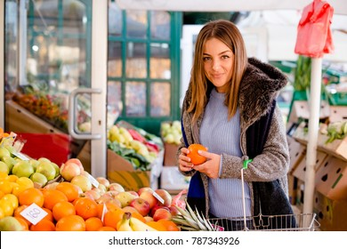 Portrait of beautiful woman holding orange, fruits and vegetables at market stall.