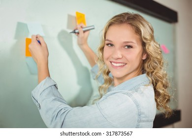 Portrait of beautiful woman holding sticky note while writing on glass board in creative office