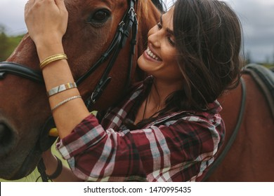 Portrait of beautiful woman and horse at the horse farm. Cowgirl petting her horse and smiling.