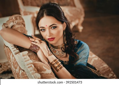 portrait of a beautiful woman in Indian traditional Chinese dress, with her hands painted with henna mehendi. Girl sitting on a luxury sofa