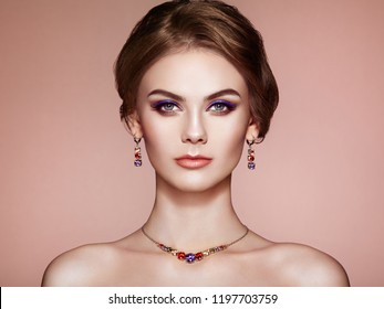 Portrait Beautiful Woman with Jewelry. Fashion Makeup and Cosmetics. Elegant Hairstyle. Violet Make-up Arrows. Beauty and Accessories