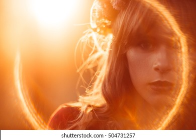 Portrait of beautiful woman, lens flare effect, free space. Close-up of female face, orange light, free space