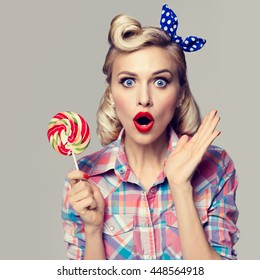 Portrait of beautiful woman with lollipop, dressed in pin-up style. Caucasian blond model posing in retro fashion and vintage concept studio shoot.