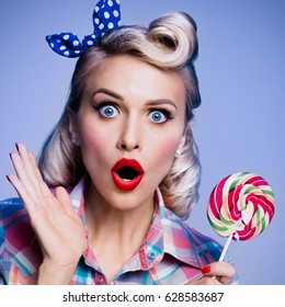 Portrait of beautiful woman with lollipop, dressed in pin-up style. Caucasian blond model posing in retro fashion and vintage concept studio shoot, blue background