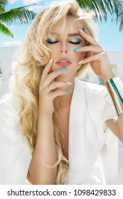 Portrait of a beautiful woman with long blond hair and elegant fingernails.