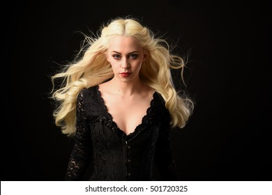 portrait of a beautiful woman with long blonde hair blowing in a wind, wearing long black gothic costume. isolated against a black background.