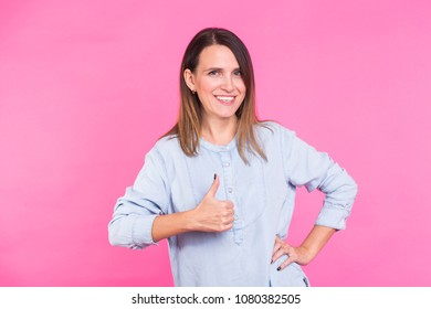 Portrait of a beautiful woman with long brown hair wearing blue cotton blouse showing thumbs up on a pink background