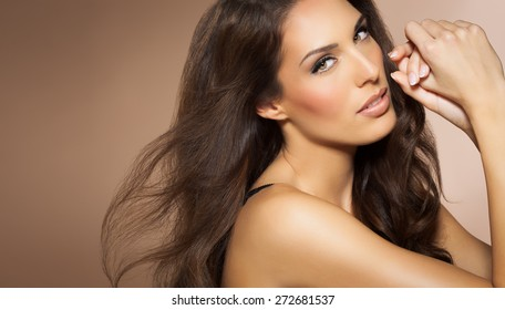 Portrait of beautiful woman with long brunette fashion hair style. Elegant Latina model with long dark hair.