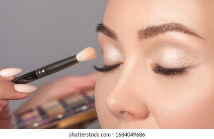Portrait of a beautiful woman with long eyelashes, beautiful make-up, thick eyebrows and with clean skin in a beauty salon. Eyelash extensions.  Makeup and cosmetology concept.