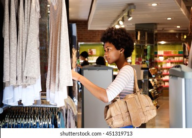 Portrait of beautiful woman looking for clothes in store