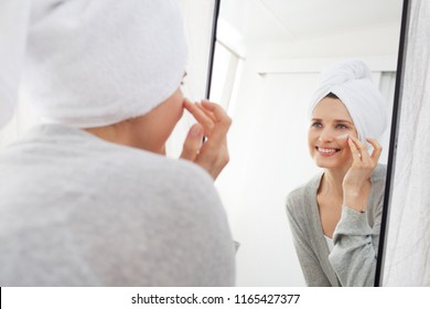 Portrait of beautiful woman looking into mirror in bathroom applying cream on face, healthy grooming skin care cosmetics. Mature female reflection with towel on hair wearing robe, wellness lifestyle.