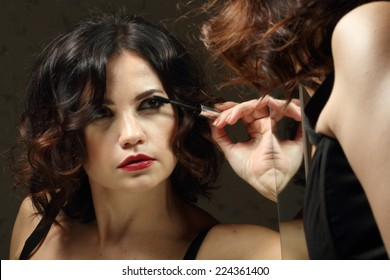 Portrait of beautiful woman looking at the mirror