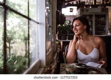 Portrait of a beautiful woman looking through window while sitting in conservatory or sunroom.