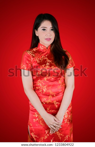 Portrait of beautiful woman looks shy while wearing cheongsam dress and standing in red background