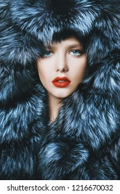 Portrait of a beautiful woman in luxurious fur coat posing in interior. Luxury, rich lifestyle. Fashion shot.