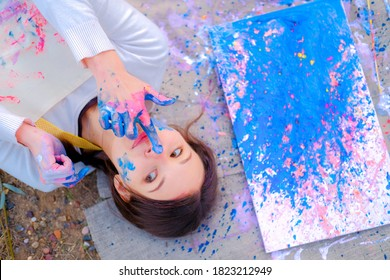 Portrait of a beautiful woman lying on the ground with Abstract blue painting on canvas using liquid acrylic technique. Face stained with paint.