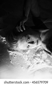 Portrait of beautiful woman lying on the floor with flour