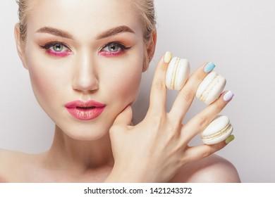 Portrait of beautiful woman with macarons, studio shoot