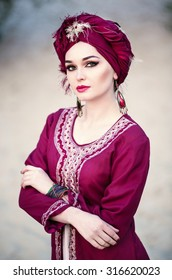 Portrait of a beautiful woman with make-up in the Arab east suit and turban, sitting in the desert, closeup