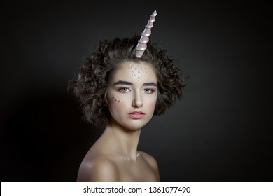 portrait of a beautiful woman with a make-up and beads on her face , pink horn , unicorn , fashion photo shoot