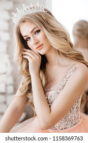 Portrait of beautiful woman with makeup in fashion clothes and crown
