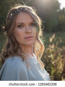 Portrait of beautiful woman with makeup and hairstyle wearing light blue dress in summer field at sunset
