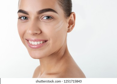 Portrait of beautiful woman with makeup smears on face against white background