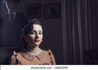 Portrait of beautiful woman, man on background, 1950s