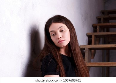 Portrait of beautiful woman in melancholy with stairs on the background