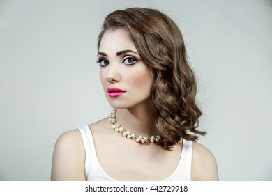 Portrait of beautiful woman model with big blue eyes and wavy hairstyle. Pink lips, long dark eyelashes and dark eyebrows makeup. Isolated on grey background.