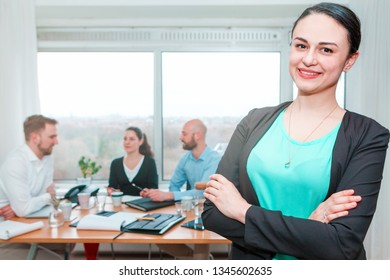 portrait of a beautiful woman in office with colleagues on background - warm filter