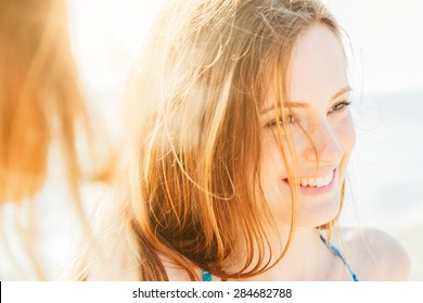 Portrait of a beautiful woman on the beach at sunset. Close-up while smiling and joking with friends after a day of relaxation and fun in the summer break.