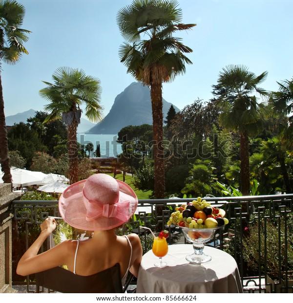 portrait of beautiful woman on the terrace of prestigious hotel.back view