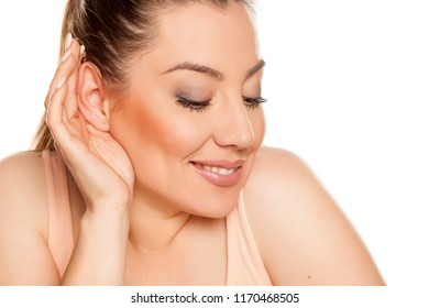 Portrait of beautiful woman on white background with palm behind her ear