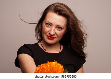 Portrait of a beautiful woman on a white background red lips with a flower in her hand