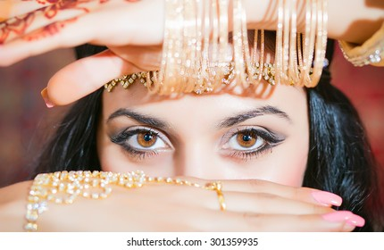 Portrait of a beautiful woman in oriental dress. Grace and beauty. Beautiful Oriental eyes closeup.Hands with gold bracelets cover the face, increased emphasis on the eyes. Luxury and beauty
