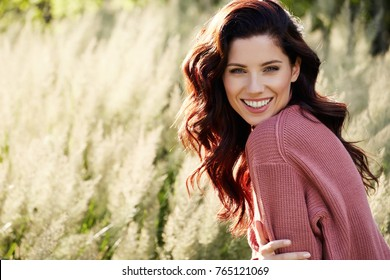 Portrait of a beautiful woman outdoors in a pink sweater