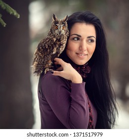 Portrait of beautiful woman with owl on her shoulder. Image with selective focus and toning.
