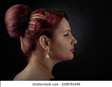 Portrait of a beautiful woman with perfect hair and makeup on a black background . Girl with pearl earrings .