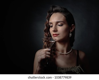 Portrait of a beautiful woman with perfect long hair and makeup .Attractive girl with  glass of martini on a black background . Studio shot .